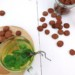 Crunchy Koolhydraatarme kruidnootjes, op een plakje met een kopje verse muntthee